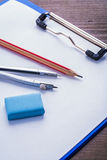 Pencil eraser compass and  clipboard with paper on Royalty Free Stock Photography