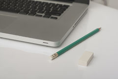 Pencil and eraser next to laptop Stock Photos