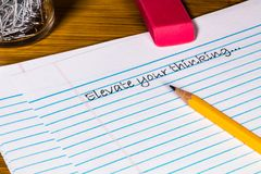 A 2 Pencil, Eraser, paper clips and Filler paper with plenty of room for Copy. Several sheets of filler paper are feathered below. The words `Elevate Your royalty free stock photo