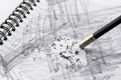Pencil eraser. With eraser dust on notebook, remove pencil drawing from notebook in close up view, mistake and error concept Stock Photography