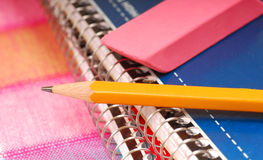 Pencil and eraser resting on notebooks Stock Image