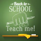 Pencil in the fist on the chalkboard with back to. School greeting Royalty Free Stock Photo