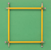 Pencil Frame. Four yellow number 2 pencils arranged to form a square frame or border on a green background Stock Photo