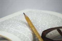 Pencil and glasses on a book. Students Studying a book - education homework Stock Photo