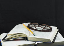 Pencil and glasses on a book. Students Studying a book - education homework Stock Image