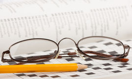 Pencil and glasses on a crossword puzzle Royalty Free Stock Photography