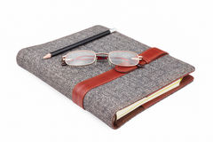 Pencil, glasses on notebook on white Royalty Free Stock Image