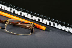 Pencil glasses and a writing-book Royalty Free Stock Images