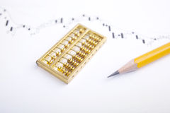 Pencil and gold abacus chart Stock Image