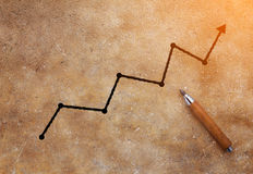 Pencil with graph drawing on brown concrete background.jpg Stock Image