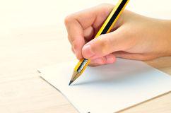 Pencil in hand writing Royalty Free Stock Image