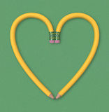 Pencil Heart. Two yellow pencils forming the outline of a heart on green paper background. Includes clipping path Royalty Free Stock Photo