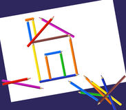 Pencil House. Illustration of a house made of pencils on paper and several other color pencils Stock Photo