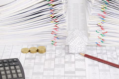 Pencil and house with coins have dual document as background. Pencil and house with step pile of gold coins on finance account have calculator and dual pile Stock Photography