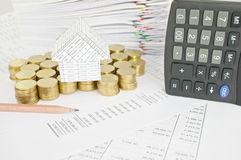 Pencil with house on gold coins and calculator place vertical Stock Image