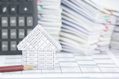 Pencil and house have blur calculator and paperwork as background Stock Image