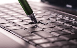 Pencil on keyboard. Using a laptop, pencil on laptop keyboard Royalty Free Stock Photography