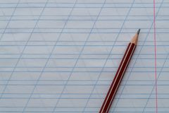 The pencil lies on top of the notebook in the oblique ruler. Top view. Copy space royalty free stock images