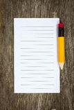 Pencil and lined paper. On the wood background Stock Photography