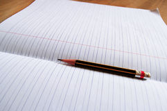 Pencil lying on a blank paper Royalty Free Stock Images