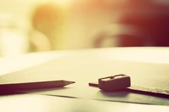 Pencil lying on blank paper in morning light. Penci, ruler and sharpenerl lying on blank piece of paper in morning light. Creative work, drawing etc. Vintage Royalty Free Stock Photography