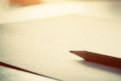 Pencil lying on blank paper in morning light. Royalty Free Stock Photo