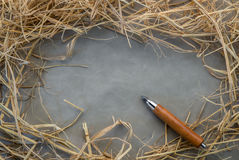 Pencil lying on blank piece of cloth and dry hay Stock Photos