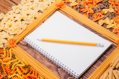 Pencil lying on a book of recipes frame of pasta Royalty Free Stock Image