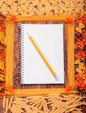 Pencil lying on a book of recipes frame of pasta Royalty Free Stock Images