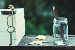 Free Pencil Made Of Wood In Glass Bottle, Vintage Key And Book Stack On Wooden Table With Morning Light And Blur Green Garden Stock Photo - 134015080