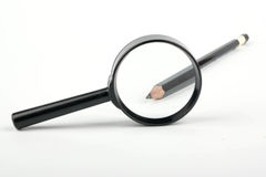 Pencil in a magnifying glass Royalty Free Stock Images