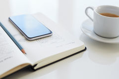 Pencil and mobile phone lying on an open diary Royalty Free Stock Photo