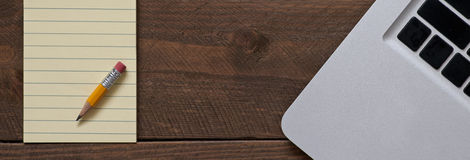 Pencil on the note pad and the computer Royalty Free Stock Photos
