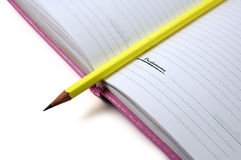 Pencil and notebook. Yellow pencil and pink notebook Royalty Free Stock Photography