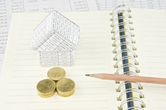 Pencil on notebook with gold coin and house Royalty Free Stock Photography
