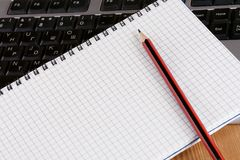 Pencil and notebook on keyboard Royalty Free Stock Photo