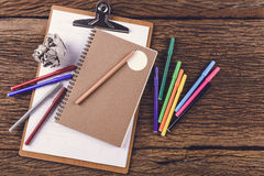 Pencil with notebook and Magic Colors on Wooden background Stock Images