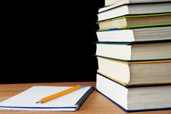 Pencil on notebook near pile of books Stock Photos