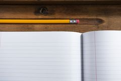 Pencil and Notebook Paper on a Wooden School Desk stock photography