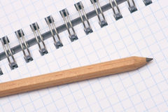A pencil and a notepad. A pencil on notepad with a spiral binding Royalty Free Stock Image