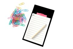Pencil on the notepad with black frame and colorful clips around on white background stock image