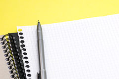 Pencil, notepad and clean sheet of paper on yellow desk backgrou Royalty Free Stock Photography
