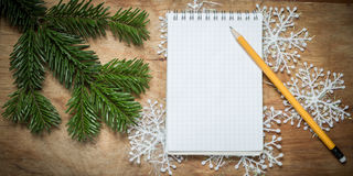 Pencil and Notepad on old rustic table decorated with a fir bran Royalty Free Stock Image