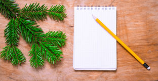 Pencil and Notepad on old rustic table decorated with a fir bran Stock Photography