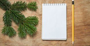 Pencil and Notepad on old rustic table decorated with a fir bran Stock Photos