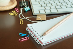 Pencil on notepad in workspace with keyboard Royalty Free Stock Photography