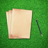 Pencil and old book on green grass Stock Images