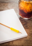 Pencil on open blank notebook with glass of iced cola Royalty Free Stock Photography