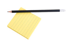 Pencil on a pack of notes on white background. Sharp black pencil on a pack of yellow lined post-it notes Royalty Free Stock Images