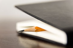 Pencil on the pages of an closed notebook for records Royalty Free Stock Images